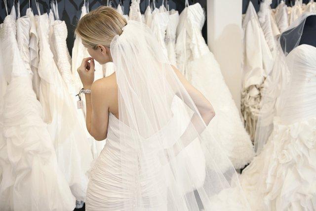 ウエディングドレスを着た女性がウェディングドレスを見ている
