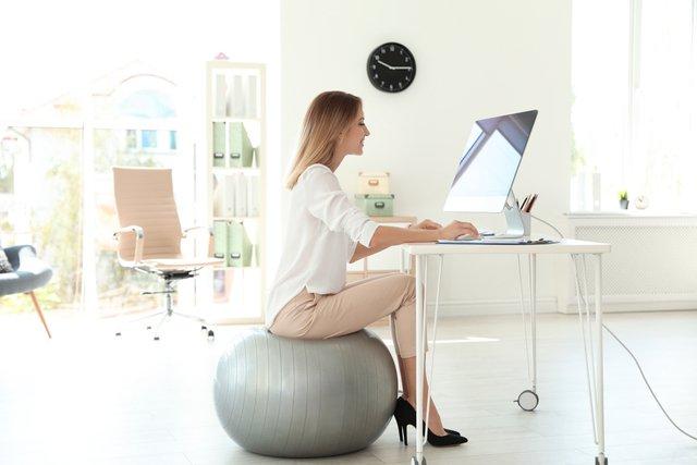 オフィスでバランスボールを使っている女性